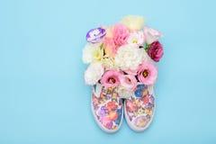 Beaux chaussures en caoutchouc avec des fleurs à l'intérieur sur le fond lumineux Image libre de droits