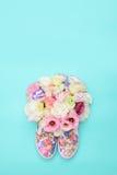 Beaux chaussures en caoutchouc avec des fleurs à l'intérieur sur le fond lumineux Images stock