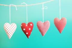 Beaux coeurs rouges de peluche accrochant sur la corde avec la belle lumière Photo libre de droits
