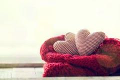 Beaux coeurs rouges de peluche avec l'écharpe chaude sur un backgroun lumineux Photo stock