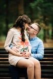 Beaux couples élégants enceintes détendant dehors en parc d'automne se reposant sur le banc Images libres de droits