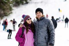 Beaux couples étreignant et riant extérieur sur une pente de ski Images stock