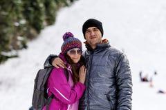 Beaux couples étreignant et souriant extérieur sur une pente de ski Photos stock