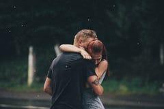 Beaux couples étreignant sous la pluie Images stock