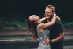 Beaux couples étreignant sous la pluie Photos stock