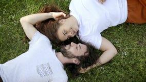 Beaux couples affectueux bouclés se trouvant sur l'herbe au parc, moment romantique banque de vidéos