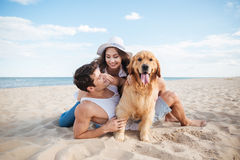 Beaux couples affectueux jouant avec leur chien au bord de la mer Photographie stock libre de droits