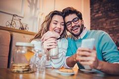 Beaux couples affectueux se reposant dans un café potable de café et à l'aide du téléphone Image libre de droits