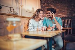 Beaux couples affectueux se reposant dans un café potable de café et à l'aide du téléphone Photos libres de droits