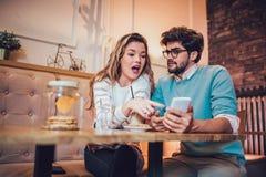 Beaux couples affectueux se reposant dans un café potable de café et à l'aide du téléphone Images stock