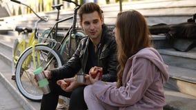 Beaux couples affectueux se reposant sur les escaliers et mangeant des croissants, du café potable dehors, se reposant sur le pla banque de vidéos