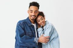 Beaux couples africains heureux dans des chemises de denim étreignant ensemble Photo stock