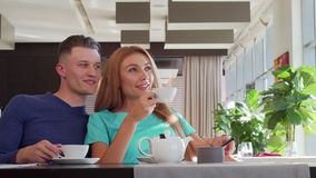 Beaux couples appréciant le thé de matin au café ensemble, regardant loin rêveusement banque de vidéos