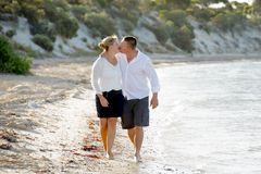 Beaux couples attrayants dans l'amour marchant sur la plage embrassant en vacances d'été romantiques Images libres de droits