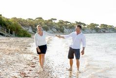 Beaux couples attrayants dans l'amour marchant sur la plage en vacances d'été romantiques Photographie stock libre de droits