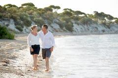 Beaux couples attrayants dans l'amour marchant sur la plage en vacances d'été romantiques Images stock