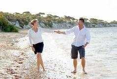 Beaux couples attrayants dans l'amour marchant sur la plage en vacances d'été romantiques Image libre de droits