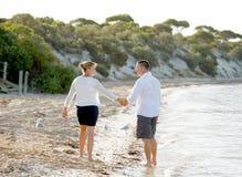 Beaux couples attrayants dans l'amour marchant sur la plage en vacances d'été romantiques Photos libres de droits