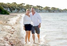 Beaux couples attrayants dans l'amour marchant sur la plage en vacances d'été romantiques Photos stock
