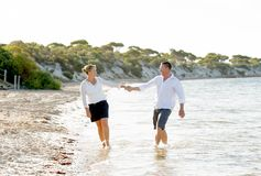 Beaux couples attrayants dans l'amour marchant sur la plage en vacances d'été romantiques Images libres de droits