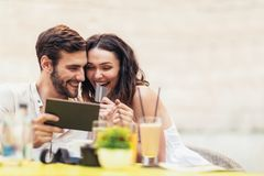 Beaux couples ayant le café une date, utilisant le comprimé numérique et la carte de crédit photos libres de droits