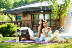 Beaux couples ayant le temps agréable mangeant des fruits dans le parc Photo libre de droits