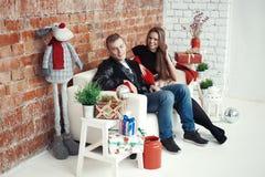Beaux couples célébrant le réveillon de Noël avec les cadeaux actuels Image stock
