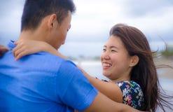 Beaux couples chinois asiatiques marchant ensemble jugeant des mains sur la plage heureuses dans l'amour appréciant des vacances Images stock