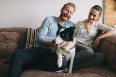 Beaux couples détendant à la maison et aimant leur chien image stock