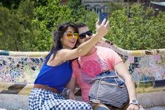 Beaux couples d'amour se reposant sur un banc en parc Guel, faisant le selfie Image stock