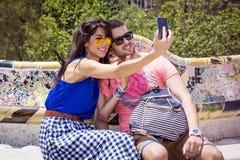 Beaux couples d'amour se reposant sur un banc en parc Guel, faisant le selfie Photo libre de droits