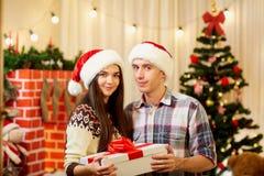 Beaux couples dans des chapeaux de Santa avec le décor dans la chambre, Photographie stock