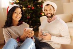 Beaux couples dans des chapeaux de Santa posant avec des tasses de café Photographie stock