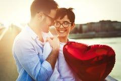 Beaux couples dans l'amour au coucher du soleil étreignant et datant Photos stock
