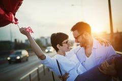 Beaux couples dans l'amour au coucher du soleil étreignant et datant Photographie stock