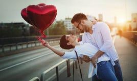 Beaux couples dans l'amour au coucher du soleil étreignant et datant Photographie stock libre de droits