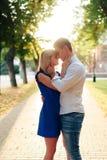 Beaux couples dans l'amour avec une femme marchant en parc sur un banc embrassant au coucher du soleil et s'aimant, une robe bleu Images stock