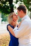 Beaux couples dans l'amour avec une femme marchant en parc sur un banc embrassant au coucher du soleil et s'aimant, une robe bleu Photo stock
