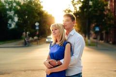 Beaux couples dans l'amour avec une femme marchant en parc sur un banc embrassant au coucher du soleil et s'aimant, une robe bleu Images libres de droits