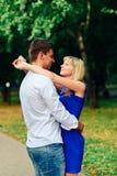Beaux couples dans l'amour avec une femme marchant en parc sur un banc embrassant au coucher du soleil et s'aimant, une robe bleu Photos stock