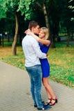 Beaux couples dans l'amour avec une femme marchant en parc sur un banc embrassant au coucher du soleil et s'aimant, une robe bleu Photos libres de droits