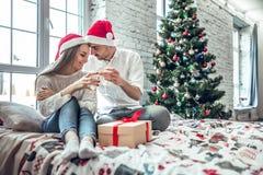 Beaux couples dans l'amour, chapeaux de port de Santa, se reposant à côté d'un arbre de Noël bien décoré et faisant un pain grill photo libre de droits