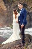 Beaux couples dans l'amour embrassant tout en se tenant sur des roches à côté de la mer Image libre de droits