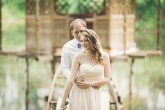 Beaux couples dans l'amour s'embrassant sur le mariage de jour, se tenant en parc dehors près du lac Photo libre de droits