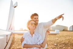 Beaux couples dans l'amour se tenant ainsi que l'avion sur le fond Images libres de droits