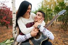 Beaux couples dans l'amour sur la nature avec une guitare images libres de droits