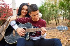 Beaux couples dans l'amour sur la nature avec une guitare images stock