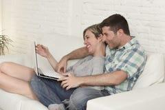 Beaux couples dans l'amour sur le divan ainsi que l'ordinateur portable Photo libre de droits