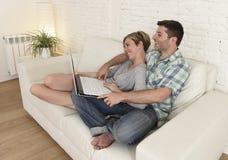 Beaux couples dans l'amour sur le divan ainsi que l'ordinateur portable heureux à la maison utilisant l'Internet Photographie stock
