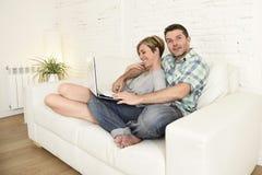 Beaux couples dans l'amour sur le divan ainsi que l'ordinateur portable heureux à la maison utilisant l'Internet Images stock